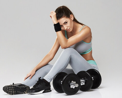 Young beautiful sportive girl in sportswear looking at camera sitting with dumbbells over white background.